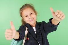 Colegiala joven sonriente que muestra los pulgares para arriba Fotos de archivo libres de regalías