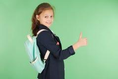 Colegiala joven sonriente que muestra los pulgares para arriba Fotografía de archivo libre de regalías
