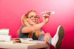 Colegiala juguetona, traviesa con las lentes grandes que lanzan el papel a Imagen de archivo libre de regalías