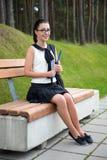 Colegiala o estudiante atractiva que se sienta en banco en parque Imágenes de archivo libres de regalías