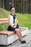 Colegiala o estudiante hermosa que se sienta en banco en parque Fotos de archivo libres de regalías