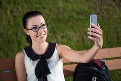 Colegiala o estudiante que hace la foto del selfie en el teléfono elegante en par Fotografía de archivo