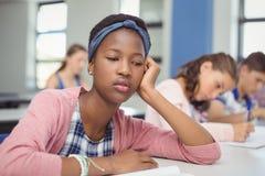 Colegiala pensativa que se sienta en sala de clase Imagen de archivo