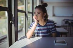 Colegiala pensativa que se sienta en sala de clase Fotografía de archivo libre de regalías