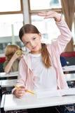 Colegiala que aumenta la mano en el escritorio en sala de clase Imagen de archivo