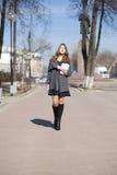 Colegiala que camina en la calle soleada de la primavera Foto de archivo libre de regalías