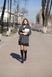 Colegiala que camina en la calle soleada de la primavera Foto de archivo