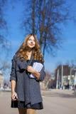 Colegiala que camina en la calle soleada de la primavera Imagen de archivo libre de regalías