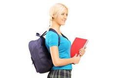Colegiala que celebra los libros de texto y caminar de la mochila Fotos de archivo libres de regalías