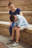 Colegiala que consuela a su amigo triste en pasos en campus Fotografía de archivo