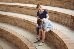 Colegiala que consuela a su amigo triste en pasos en campus Imagen de archivo libre de regalías
