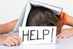 Colegiala que duerme con un libro de texto en su cabeza que lleva a cabo una muestra w Foto de archivo libre de regalías