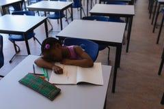 Colegiala que duerme en el escritorio en sala de clase imagen de archivo