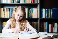 Colegiala que estudia con los libros de texto mientras que escribe en un libro Fotos de archivo