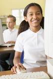 Colegiala que estudia delante de un ordenador de la escuela Fotografía de archivo