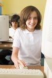 Colegiala que estudia delante de un ordenador de la escuela Imagenes de archivo