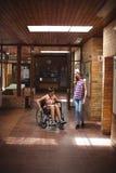 Colegiala que habla con su amigo discapacitado en pasillo Fotografía de archivo libre de regalías