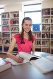 Colegiala que hace la preparación adentro en biblioteca en la escuela Fotografía de archivo libre de regalías
