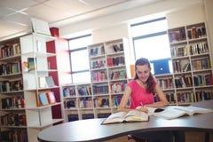 Colegiala que hace la preparación adentro en biblioteca en la escuela Imagen de archivo