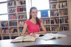 Colegiala que hace la preparación adentro en biblioteca en la escuela Imagenes de archivo