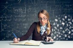 Colegiala que hace matemáticas Fotografía de archivo