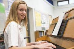 Colegiala que juega el piano en clase de música Imagen de archivo