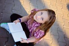 Colegiala que lee un libro Foto de archivo libre de regalías
