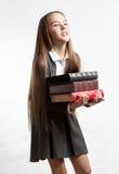 Colegiala que lleva la pila pesada de libros contra el backgroun blanco Fotos de archivo libres de regalías