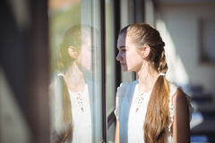 Colegiala que mira a través de ventana en sala de clase Fotografía de archivo libre de regalías