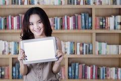 Colegiala que muestra una pantalla de la tableta en biblioteca Fotos de archivo