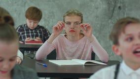 Colegiala que pone en los vidrios durante la lección almacen de video