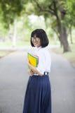 Colegiala que se coloca que sostiene un libro Imagenes de archivo
