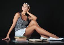 Colegiala que se sienta delante de sus libros Foto de archivo