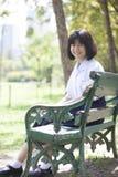 Colegiala que se sienta en el banco Fotografía de archivo