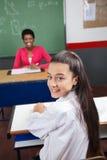 Colegiala que se sienta en el escritorio con el profesor Smiling In Fotografía de archivo libre de regalías
