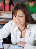 Colegiala que se sienta en el escritorio con los compañeros de clase adentro Fotos de archivo libres de regalías