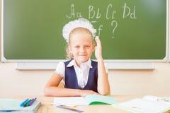 Colegiala que se sienta en el escritorio, sala de clase de la escuela, en el fondo del tablero Foto de archivo