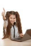 Colegiala que se sienta en el ordenador portátil Foto de archivo libre de regalías