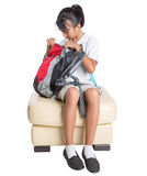 Colegiala que se sienta en el sofá con la mochila III Foto de archivo