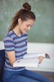 Colegiala que se sienta en silla y que sostiene un libro en sala de clase Fotos de archivo libres de regalías