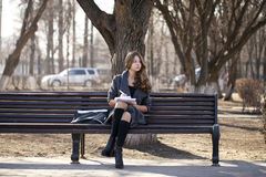 Colegiala que se sienta en un banco con un cuaderno en el parque de la primavera Imagenes de archivo