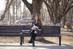 Colegiala que se sienta en un banco con un cuaderno en el parque de la primavera Fotos de archivo