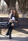 Colegiala que se sienta en un banco con un cuaderno en el parque de la primavera Imagen de archivo libre de regalías