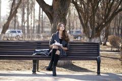 Colegiala que se sienta en un banco con un cuaderno en el parque de la primavera Fotografía de archivo libre de regalías