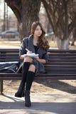 Colegiala que se sienta en un banco con un cuaderno en el parque de la primavera Imagen de archivo