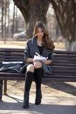 Colegiala que se sienta en un banco con un cuaderno en el parque de la primavera Imágenes de archivo libres de regalías