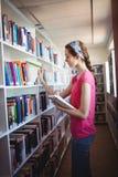 Colegiala que selecciona el libro de estante de librería en biblioteca Imagen de archivo