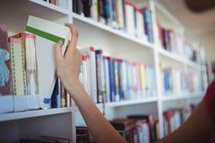 Colegiala que selecciona el libro de estante de librería en biblioteca Imágenes de archivo libres de regalías