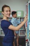 Colegiala que selecciona el libro de estante de librería en biblioteca en la escuela Imagen de archivo
