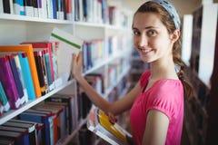 Colegiala que selecciona el libro de estante de librería en biblioteca en la escuela Imagenes de archivo